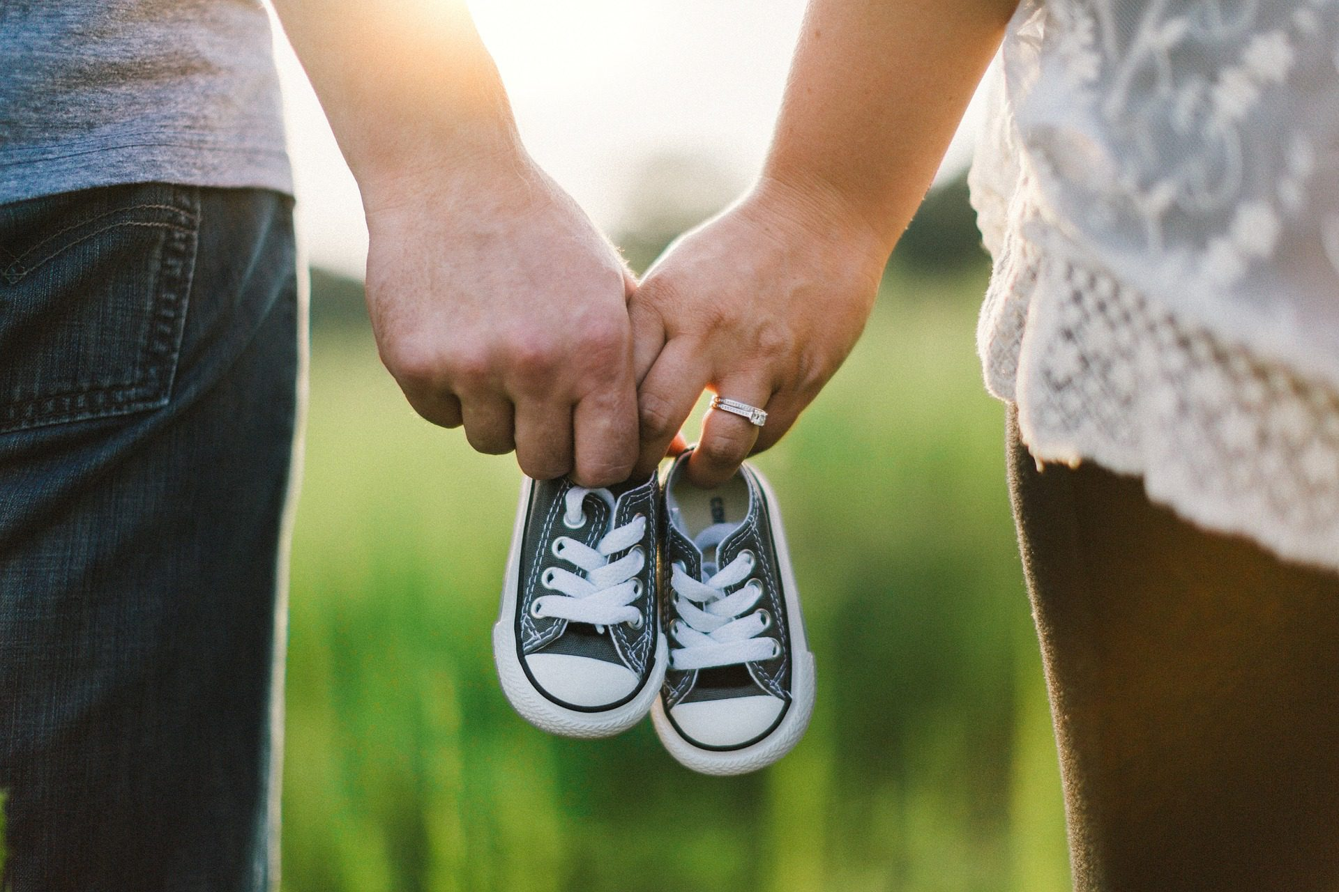 woman and man holding baby shoes