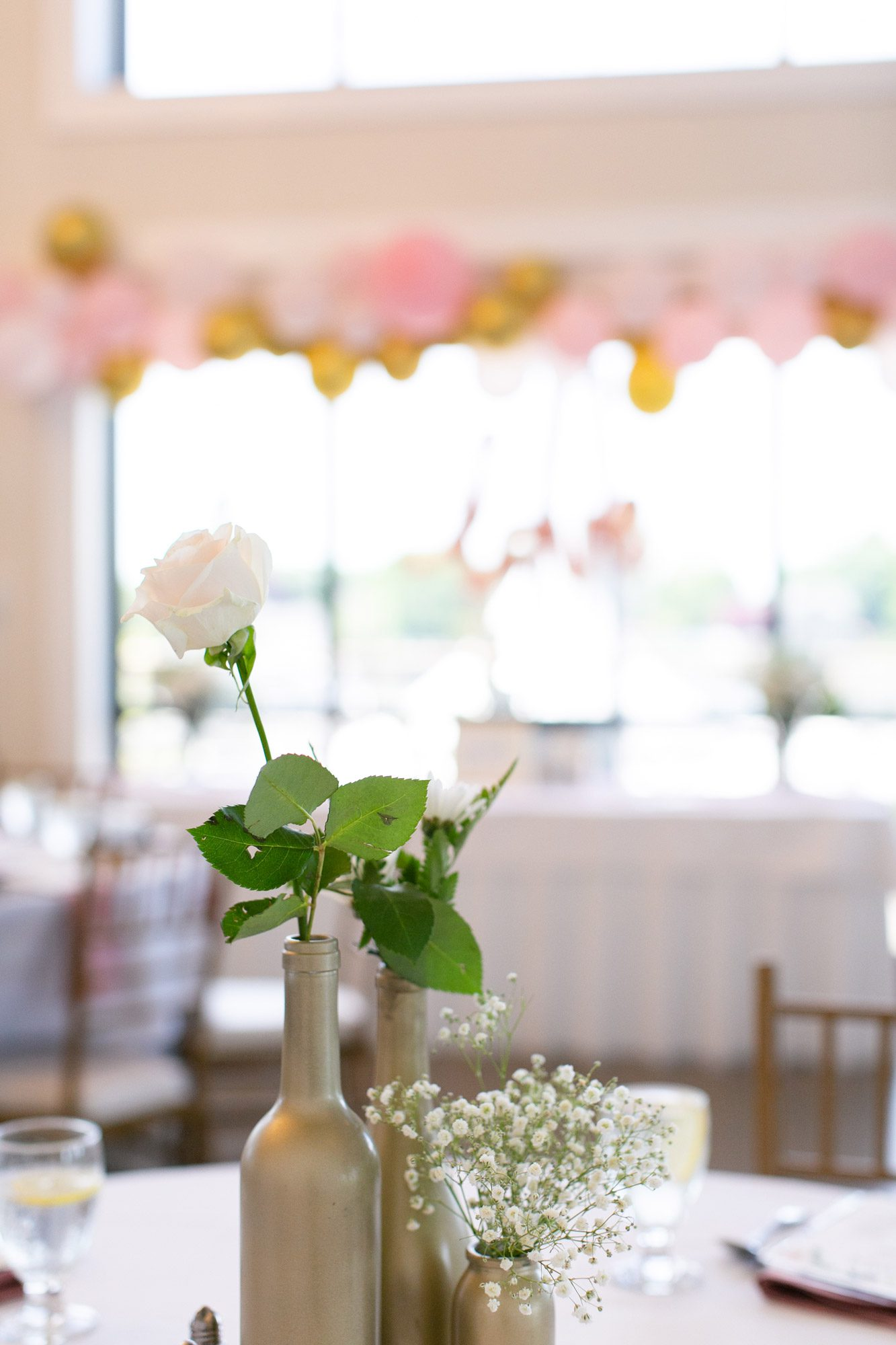 Single white roses in gold spray painted bottles as a centerpiece on a table.