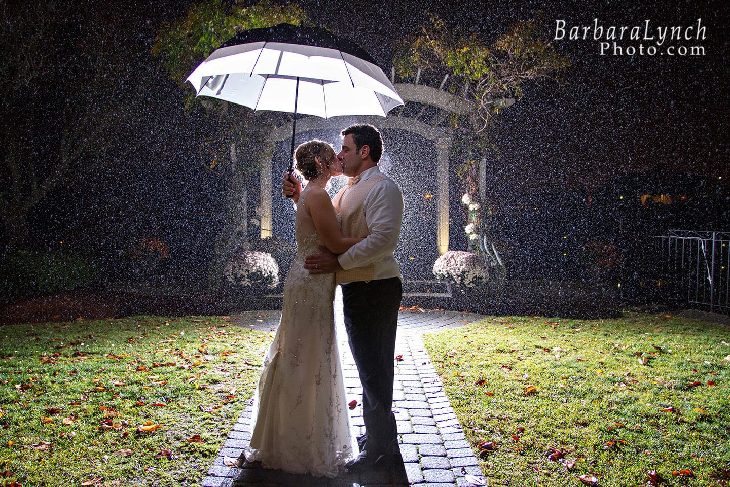 A couple kisses under an umbrella under the pergola at the Danversport Yacht Club