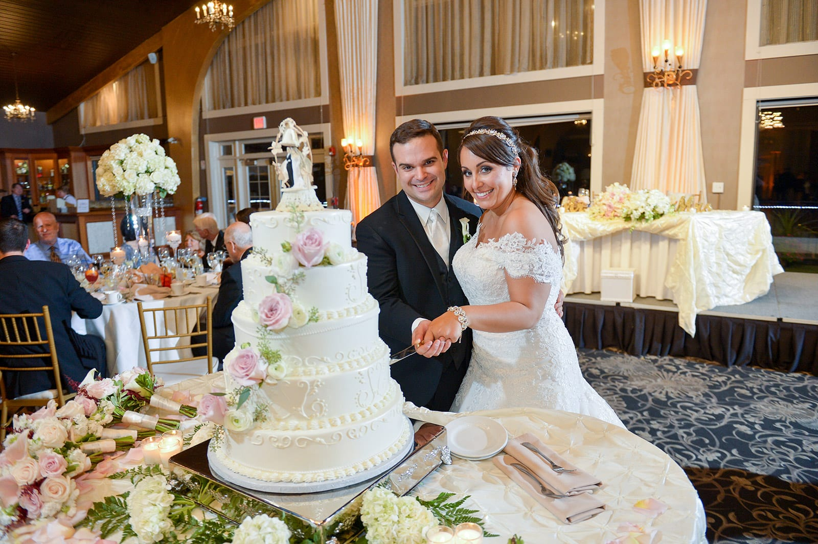 A couple smiles for the camera while cutting the cake in the Harborview Ballroom