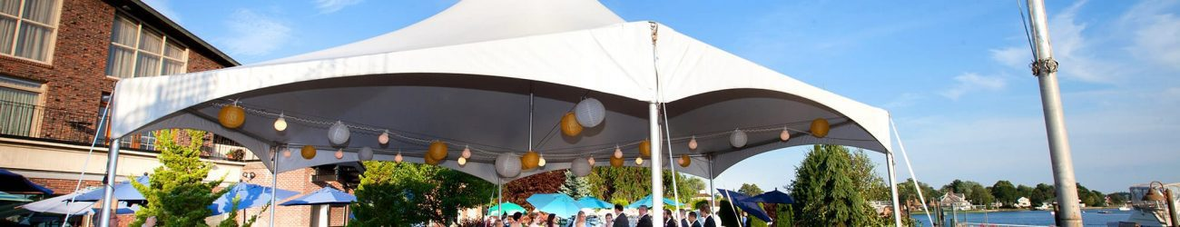 Photo of Danversport visitors gathered under a party tent attending a wedding ceremony by the water