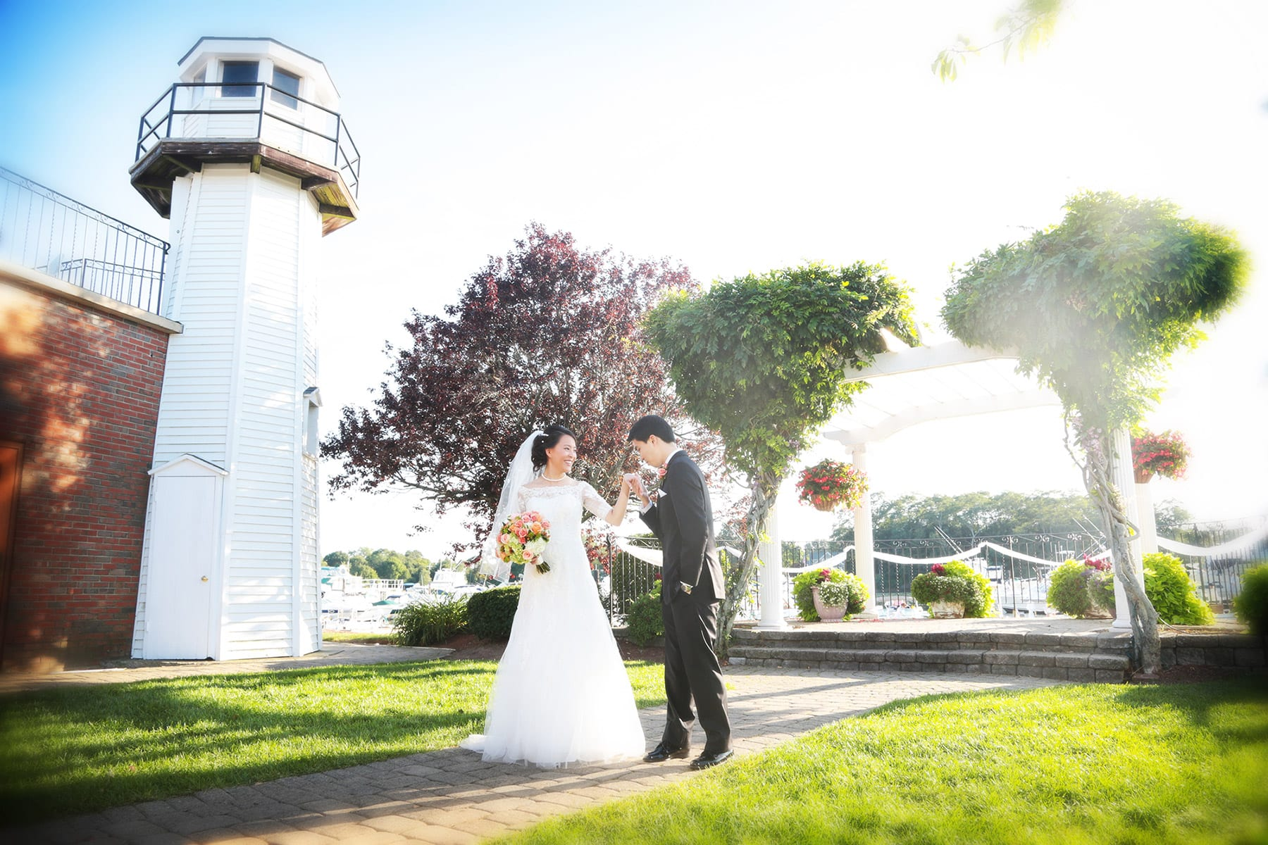 A bride and groom stand on the path leading to the Danversport Pergola