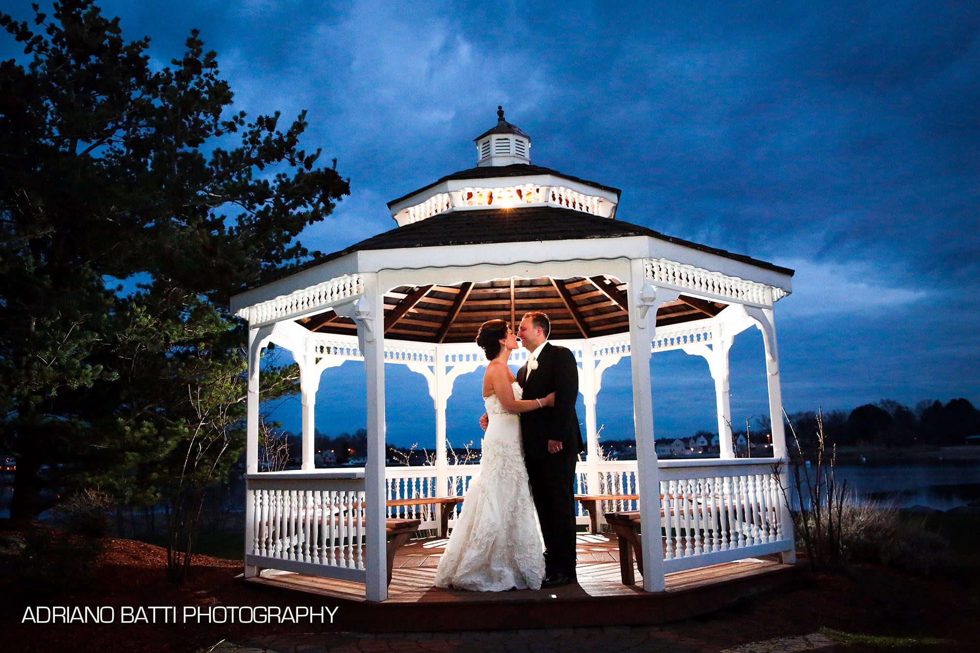 A couple stands in the backlit Danversport Gazebo by the water at dusk.