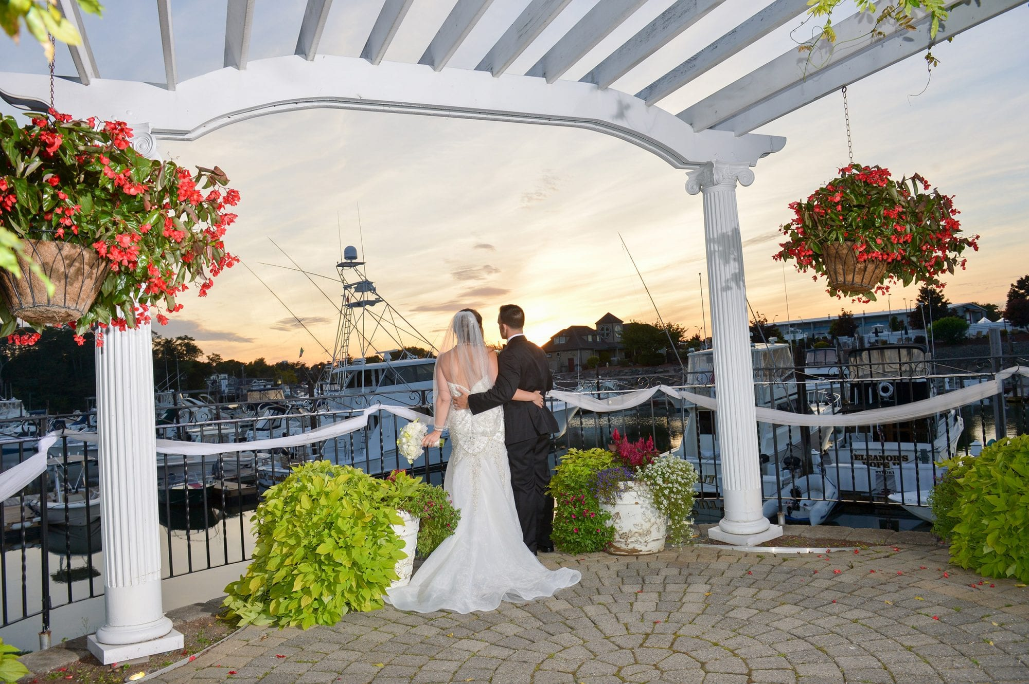 Photo of a couple from behind as they look out at the marina at sunset