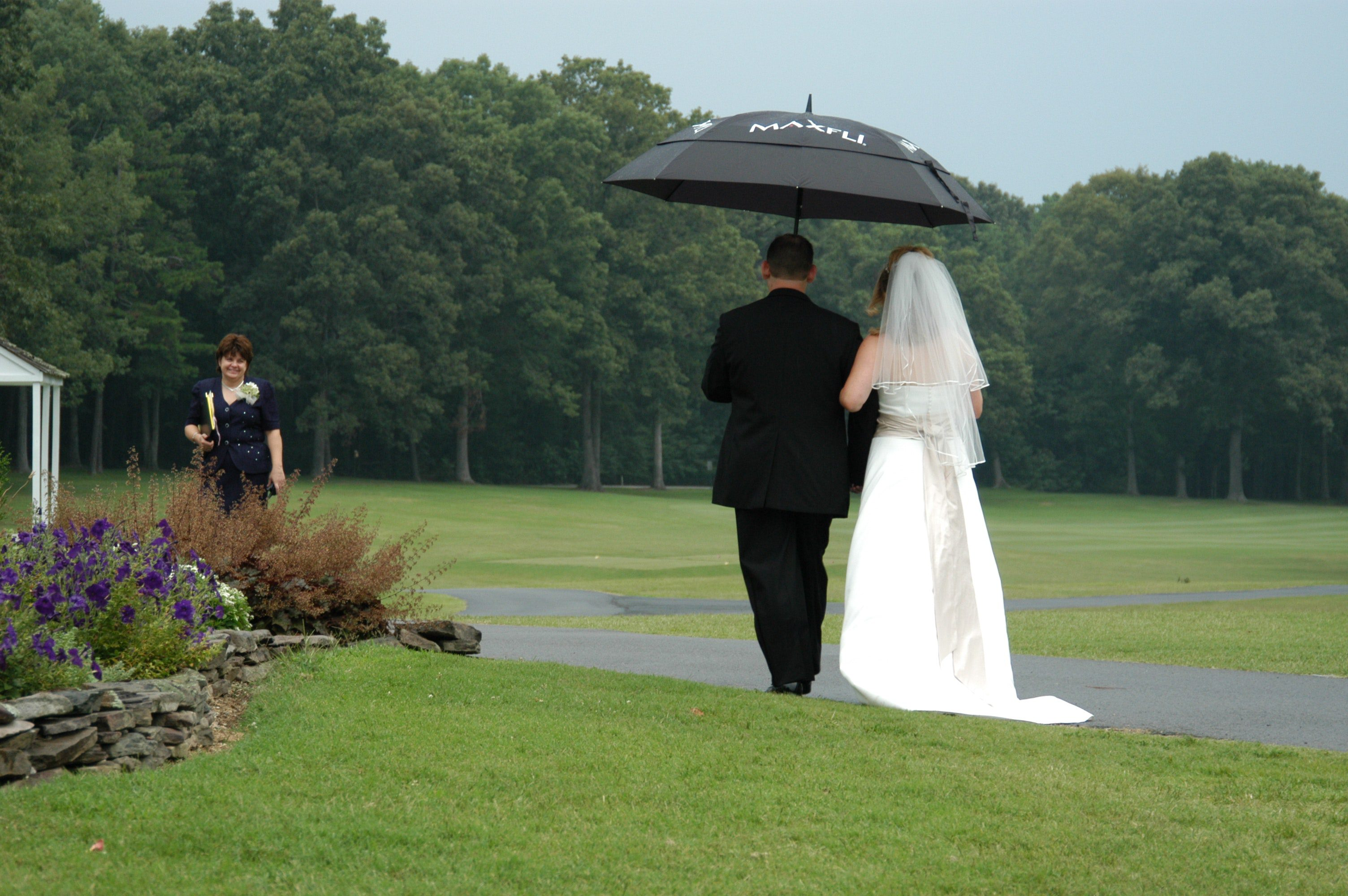 Bride and Groom walking in the rain holding an umbrella