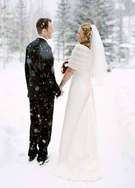 Bride and Groom standing outside while it's snowing