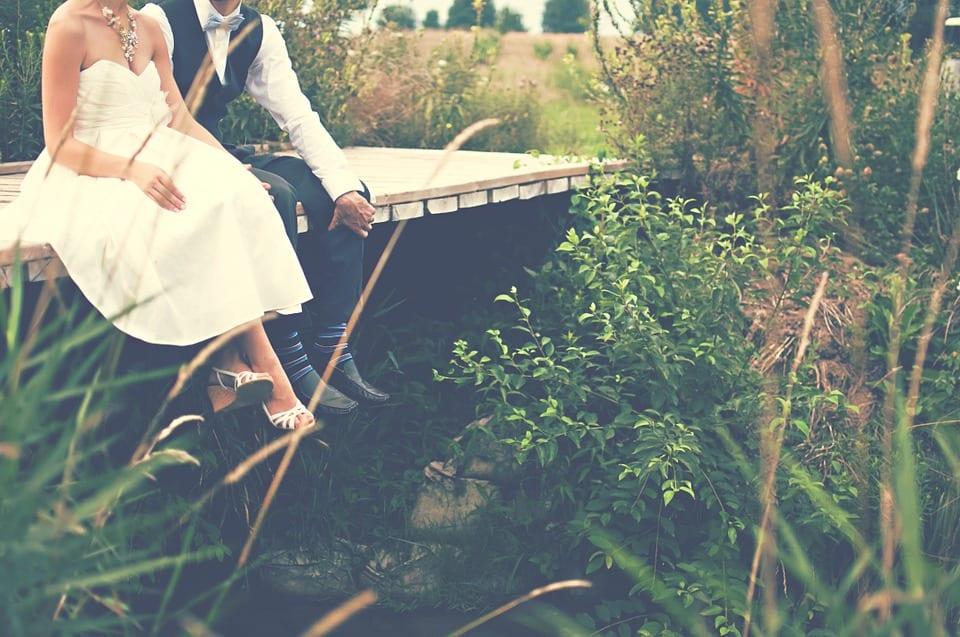 Rustic wedding and couple sitting on bridge