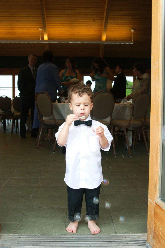 little boy at wedding blowing bubbles